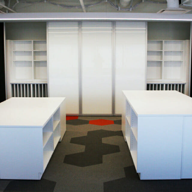 Storage Wall behind Sliding Whiteboards and Custom Islands in Workplace Design